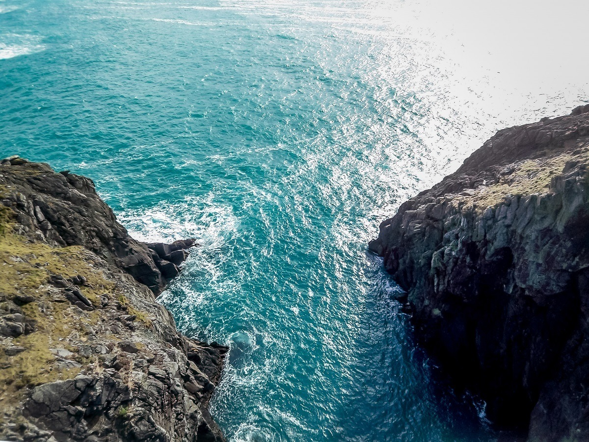 Blue ocean water under a suspension bridge