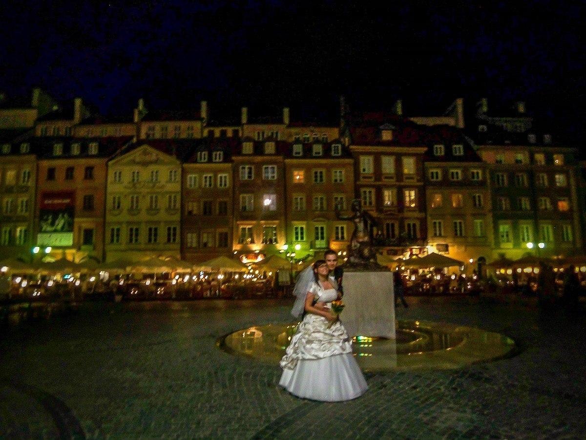 A couple having wedding photos taken in Warsaw's Old Town at night