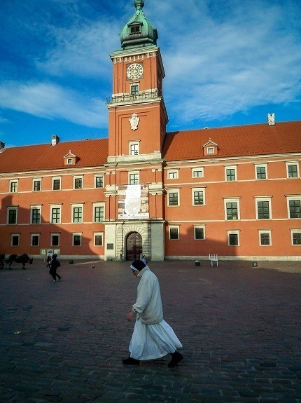 A nun walking in front of the Royal Castle in Warsaw, Poland