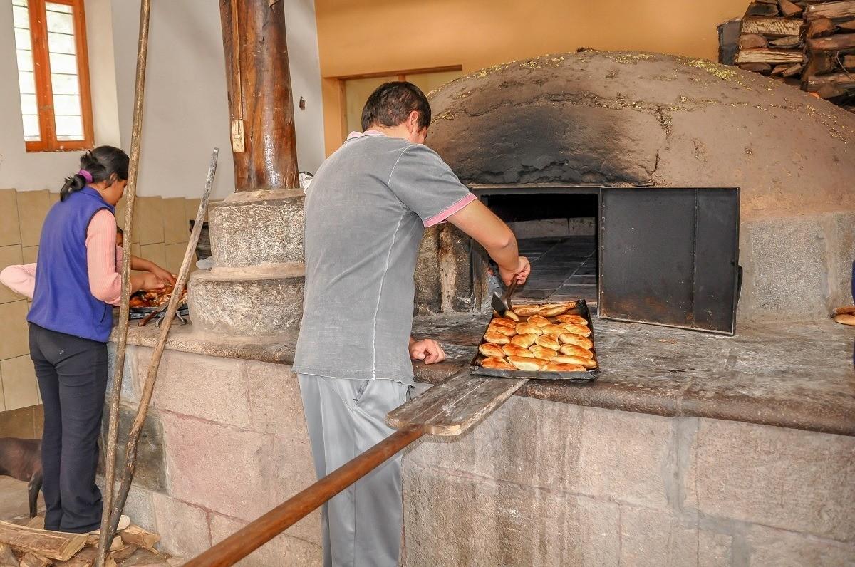 Family cooking empanadas in a mud oven in Peru