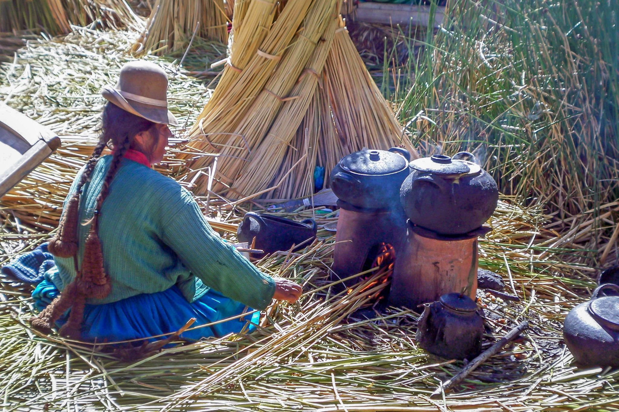 A women tending a cooking fire on the Uros Islands in Peru