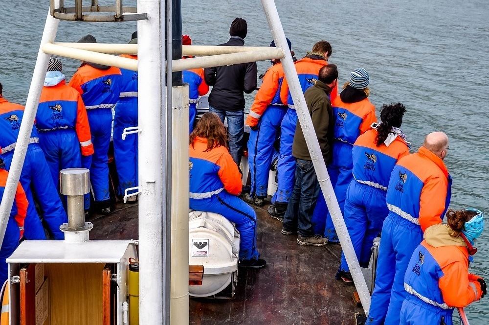 People in warm suits on a Husavik whale watching boat