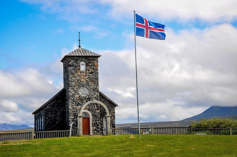 Stone building beside a flagpole