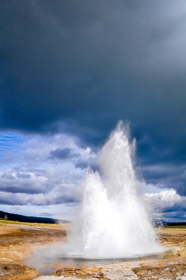 Strokkur geyser, mid-eruption, against a dark sky