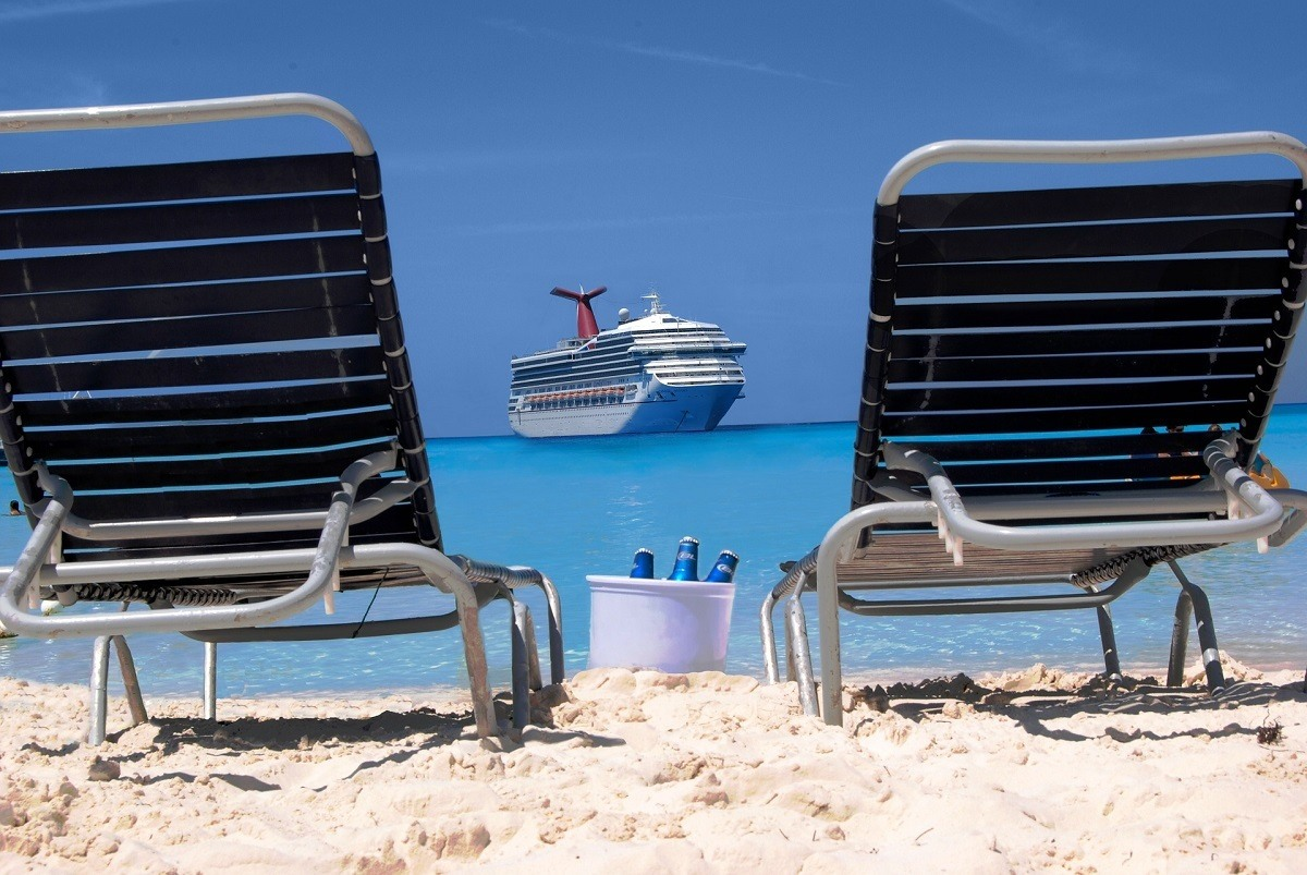 Two sun loungers and a bucket of beer looking out at a cruise ship