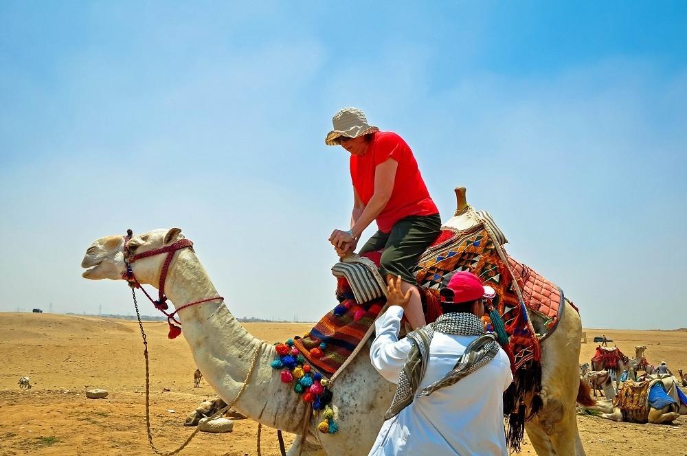 Rider boarding a camel while visiting the Pyramids of Giza