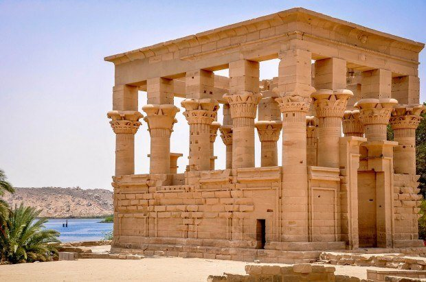 Ancient Egyptian temple with columns by a lake