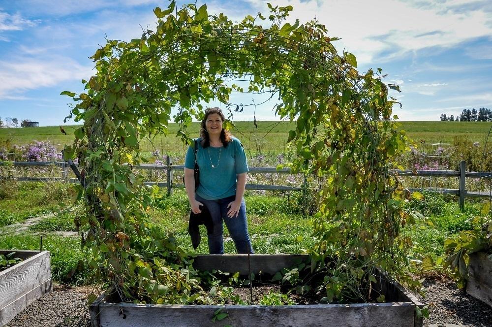 Laura standing in a vegetable garden