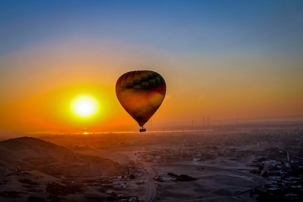 Hot air balloon at sunrise over the Valley of the Kings and Luxor