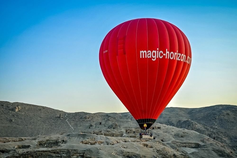 Bright red hot air balloon in Egypt taking off