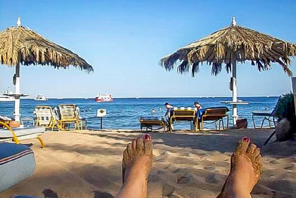 Feet hanging out on the beach with loungers and umbrellas in Sharm el Sheikh Egypt