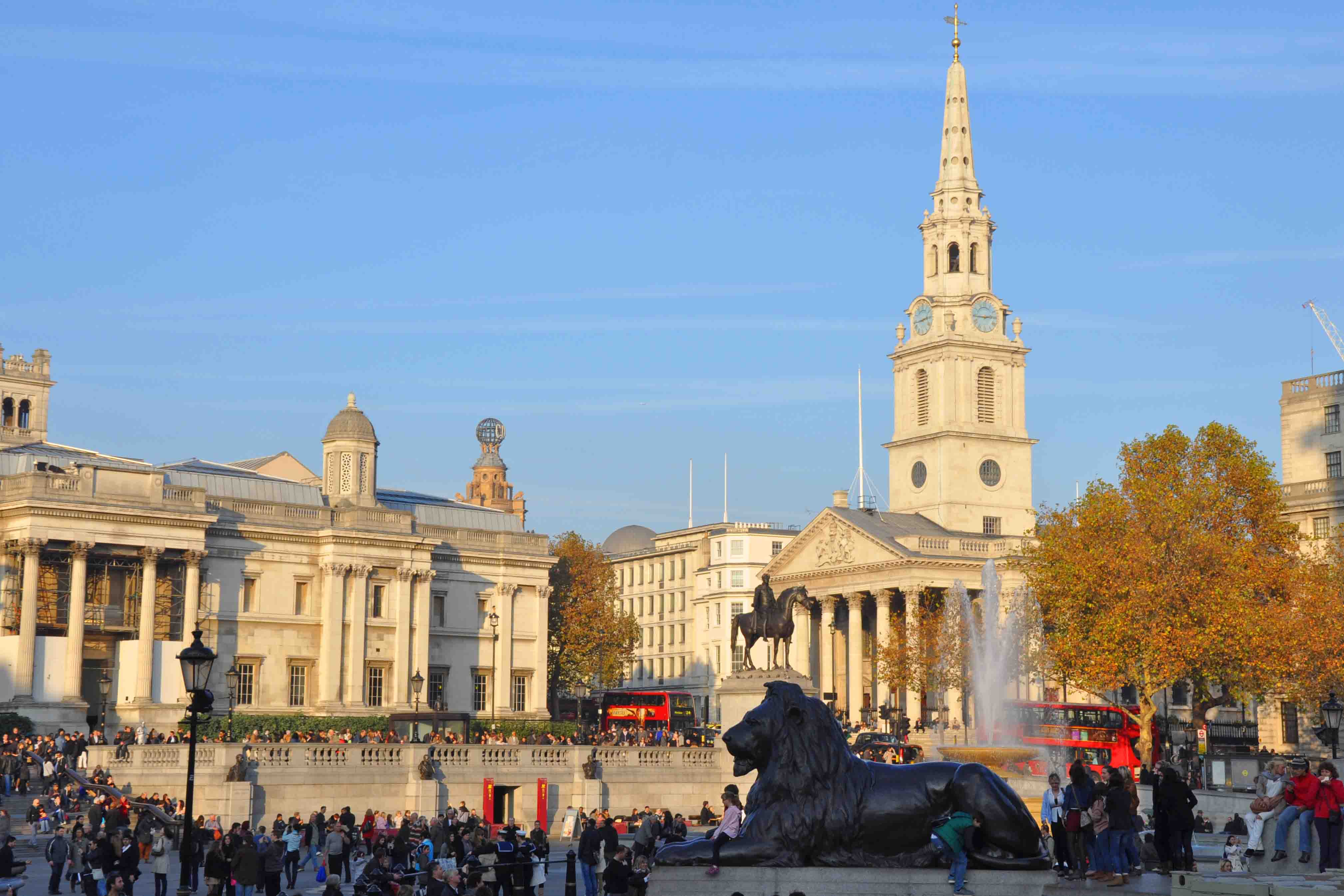 Trafalgar Square with lion sculpture and lots of people