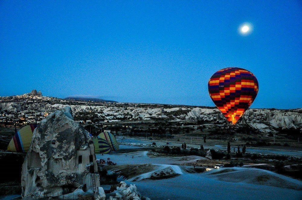 One of the Cappadocia Hot Air Balloons illuminated in the night sky under the moon