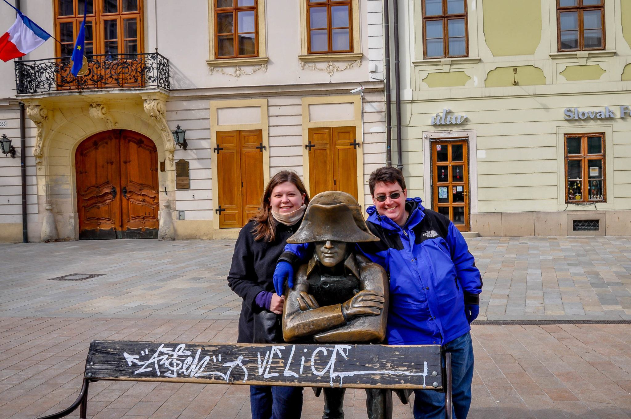 Two people posing with a statue