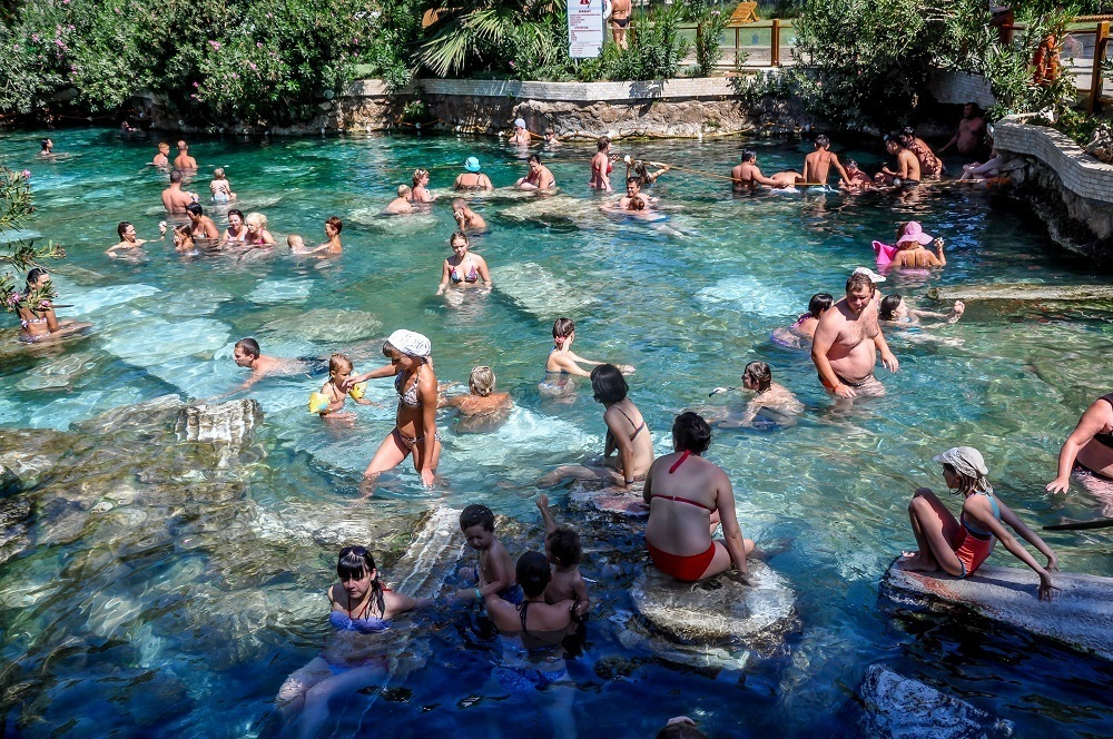 Visitors lounging in the Pamukkale hot springs antique pool