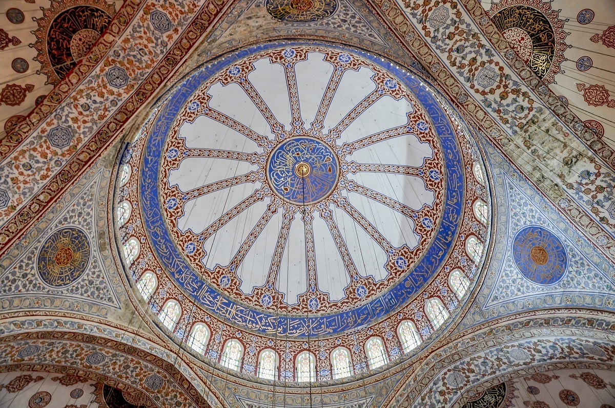 The ornate painted ceiling of the Blue Mosque, one of the top places to see in Istanbul