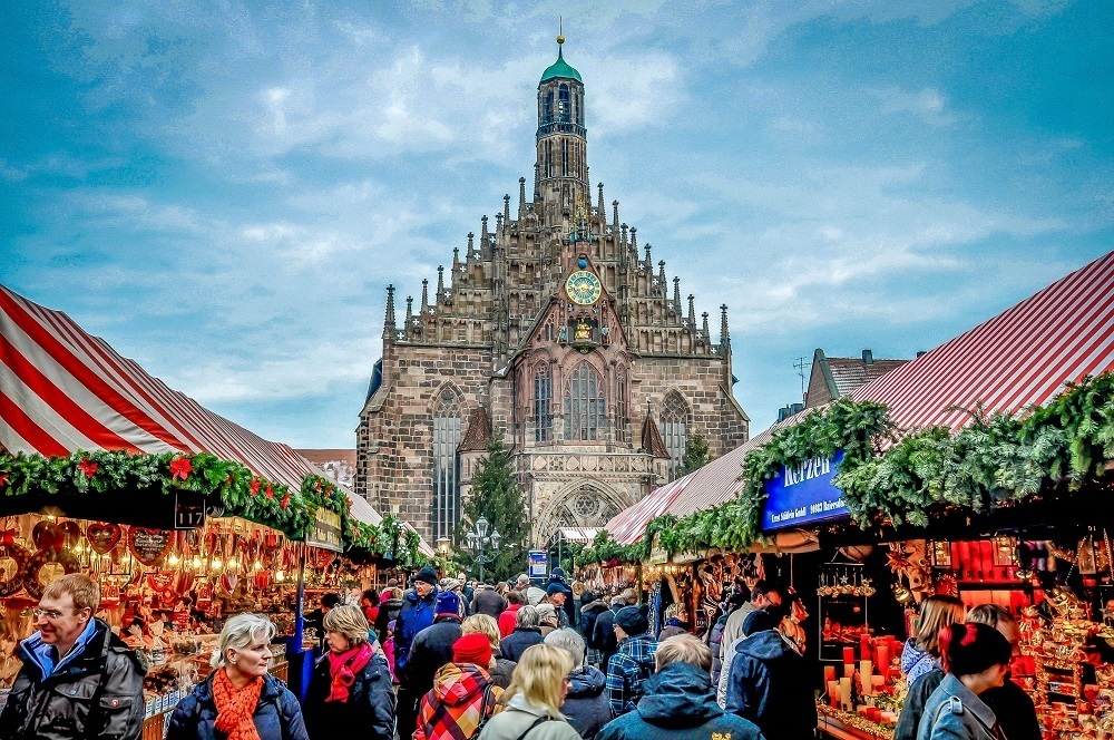 People shopping at the Nuremberg Christmas market with church in the background