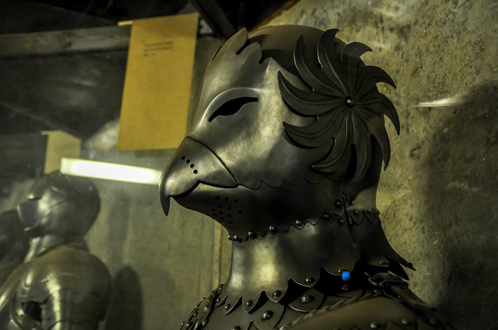 Steel helmet and face mask in bird shape inside the armory