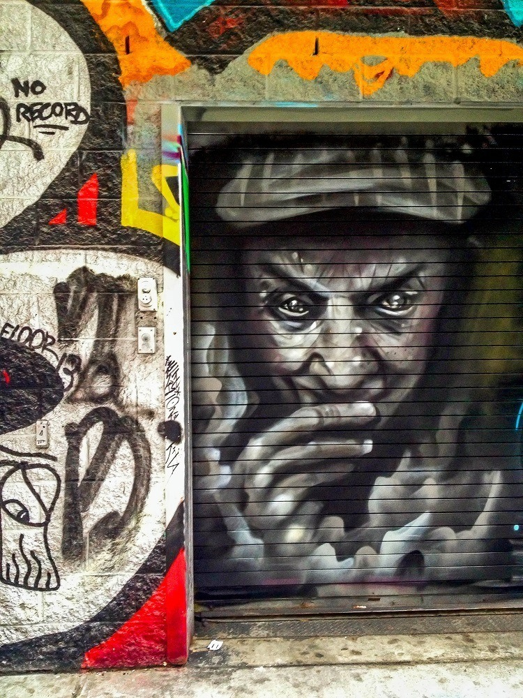 Street art featuring a sneaky man in Graffiti Alley Toronto
