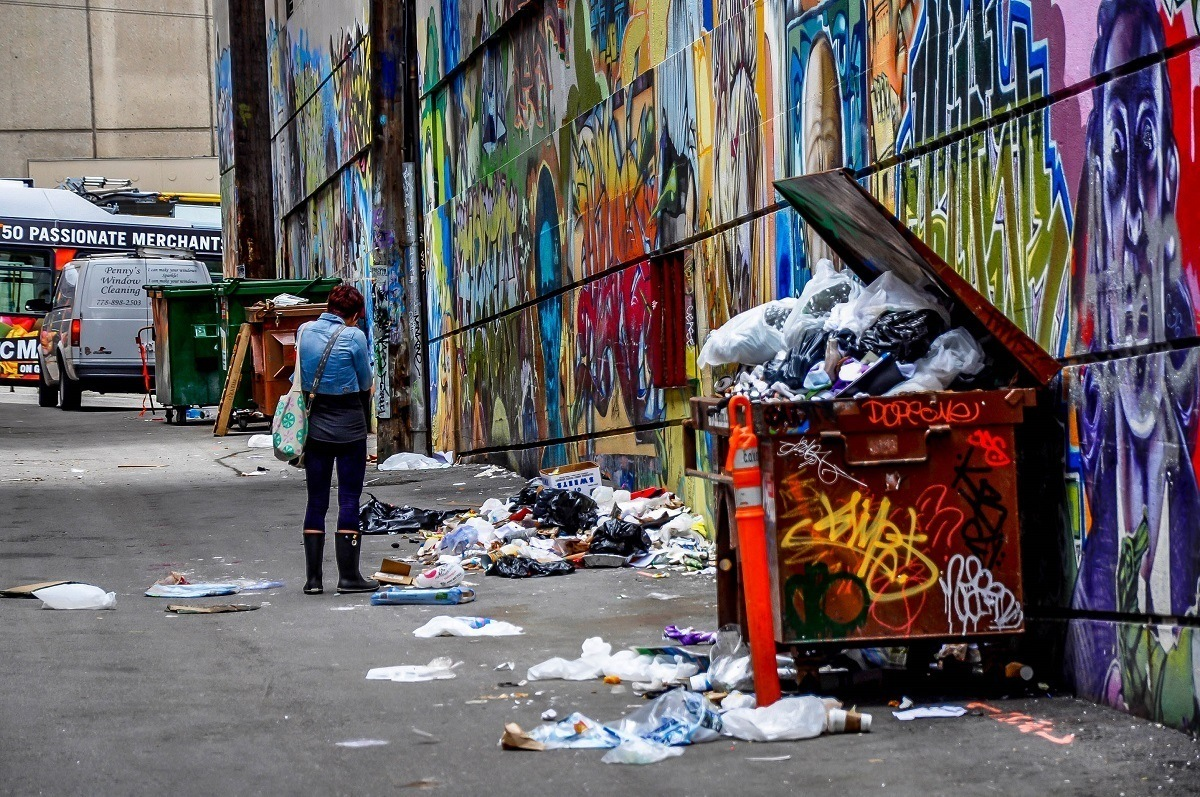 Woman smoking and looking at graffiti in alley with trash