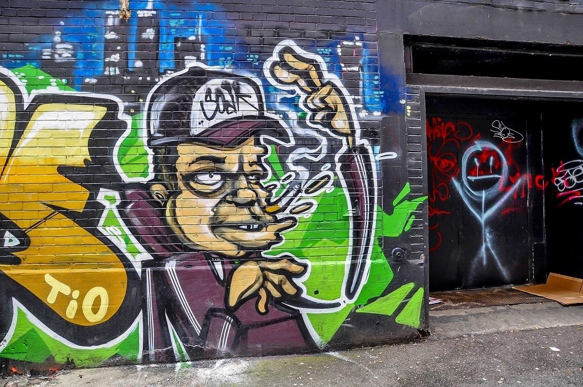 Cartoon mural in alley of man smoking