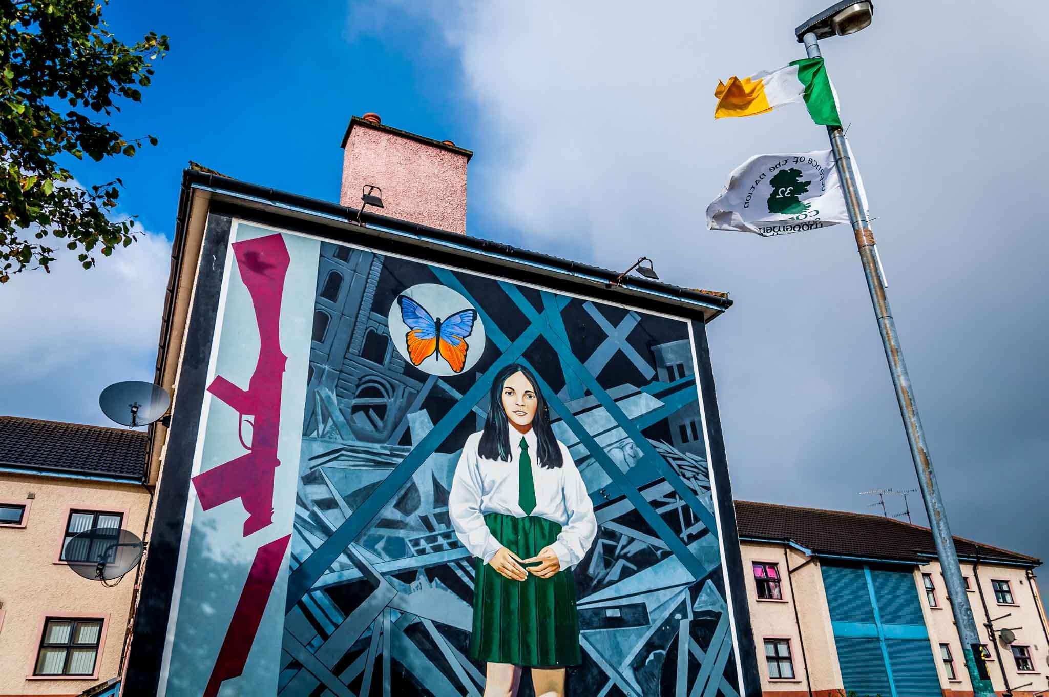 End of Innocence mural featuring girl in a school uniform alongside a broken rifle