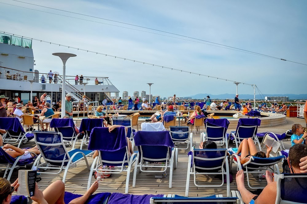 Lounge chairs on a cruise ship around the swimming pool