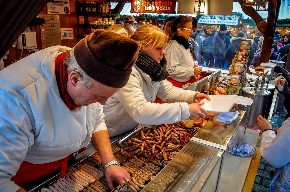 People serving sausage at the German Christmas markets