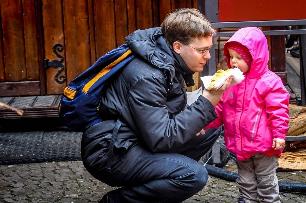 Daddy and daughter eating sausage