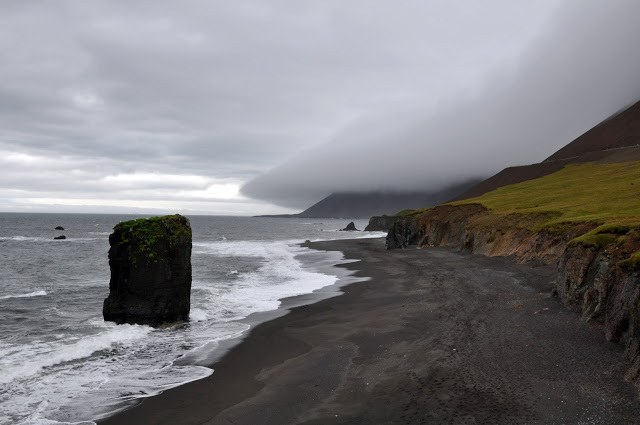 Rock formation along a black sand beach