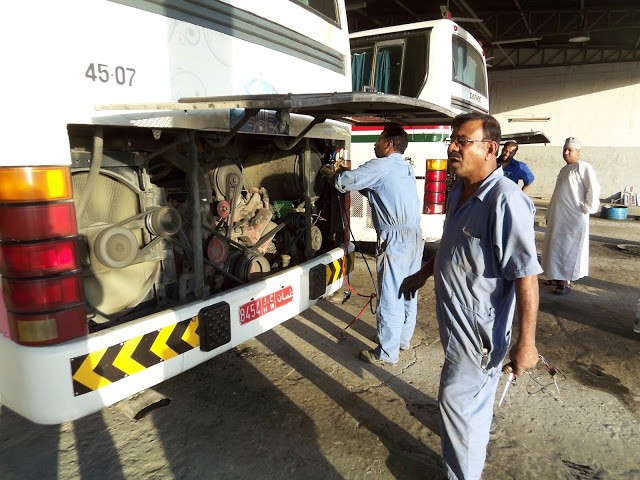Mechanics working on the Mwasalat Buses after a breakdown