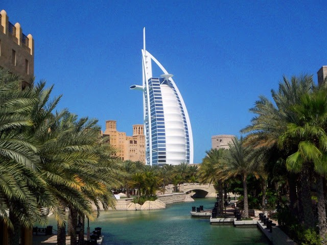 The Burj al Arab hotel, a white building shaped like a nillowing sail, surrounded by palm trees and water