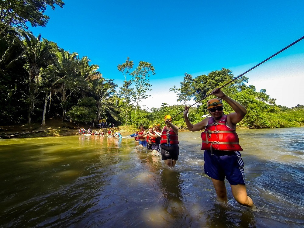 Group of people in life jackets crossing the Caves Branch River in Belize