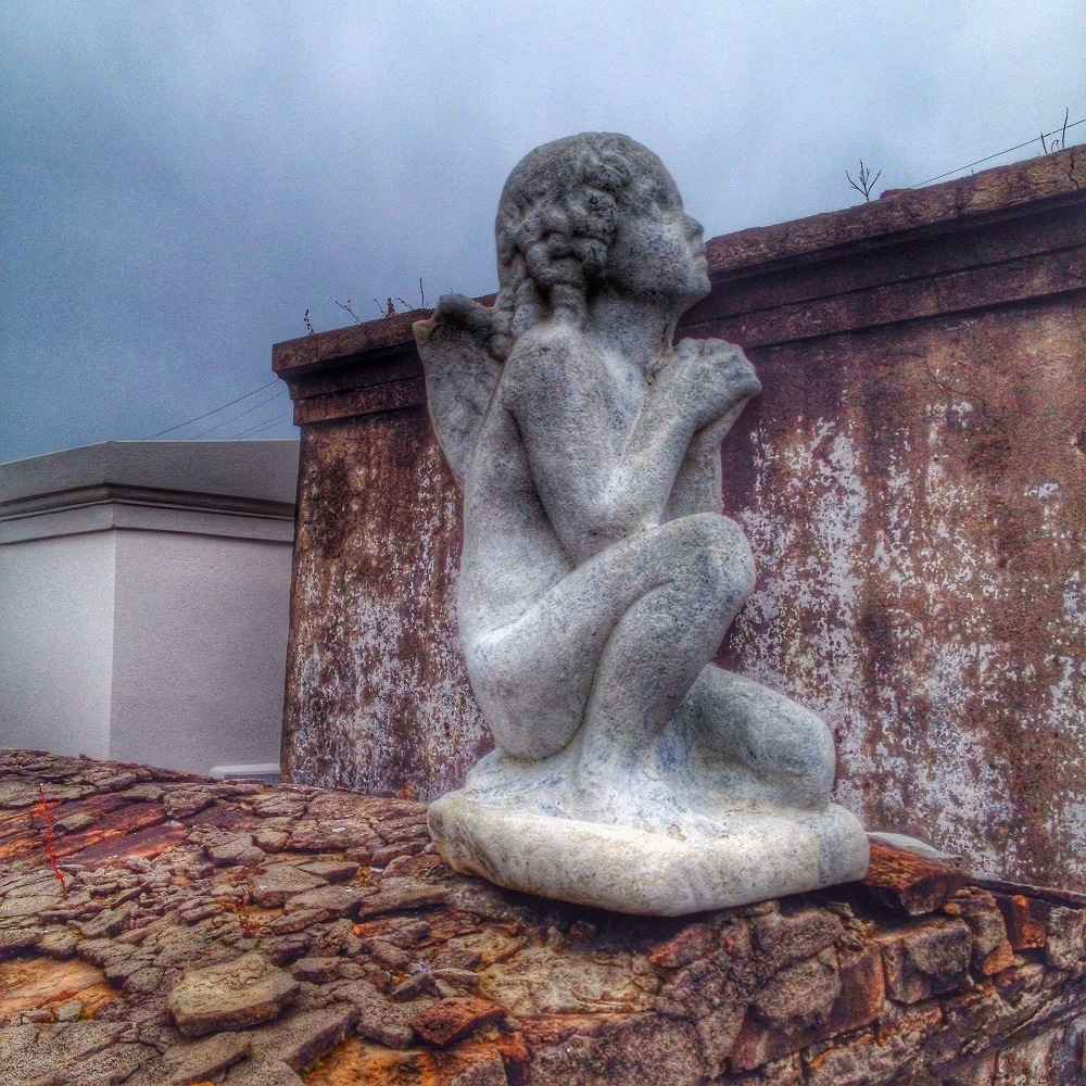 A concrete cherub on a tomb in New Orleans St. Louis Cemetery No. 1