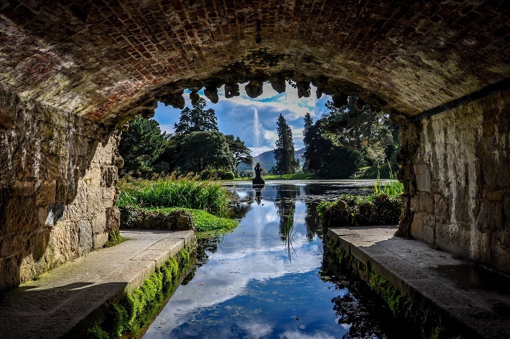 Fountain in a pond as seen through a tunnel