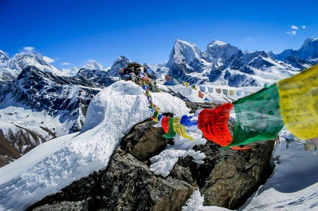 Nepalese prayer flags high in the snow covered mountains