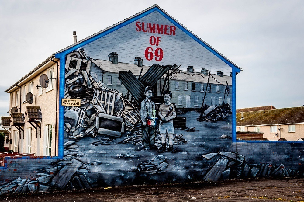 """Street art mural with the label """"Summer of 69"""" showing young boys among ruins"""