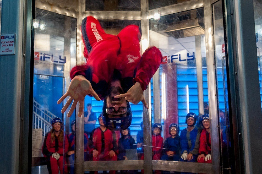 Person demonstrating indoor skydiving with spectators