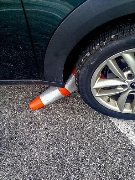 Safety cone lodged under the wheel of a  car