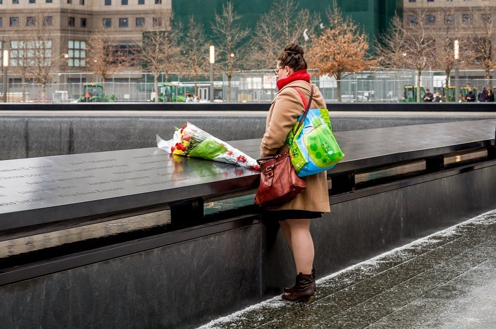 Visitor with a bouquet of flowers at the September 11 Memorial