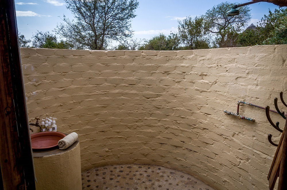 The outdoor shower in a rondavel hut
