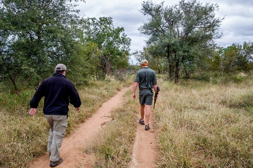 Lance with a guide with a rifle in the African bush