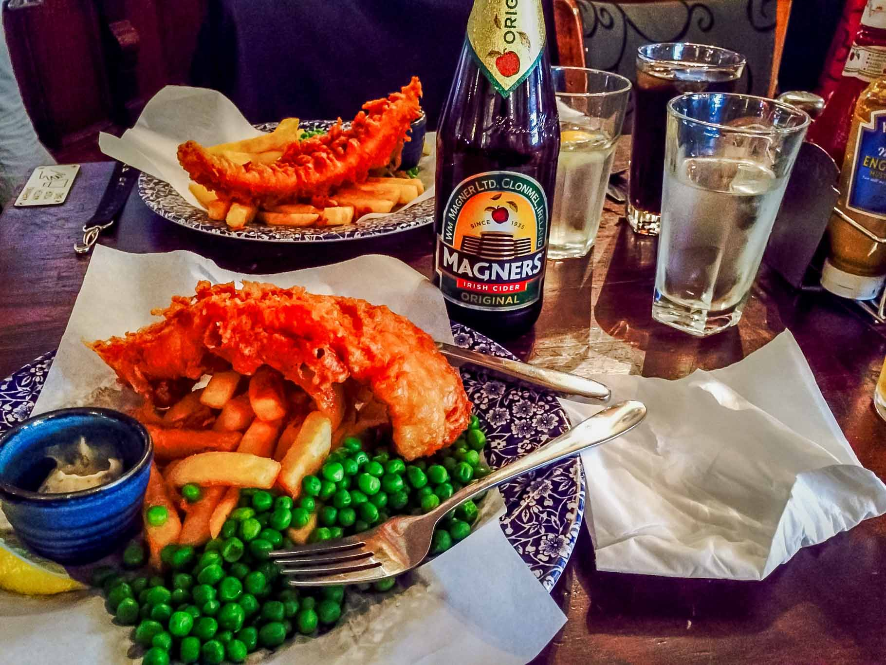 Fish and chips with cider and water on a table