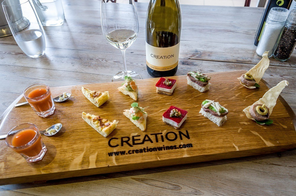 The canapés tasting board at Creation Wines with bottle and glass of wine