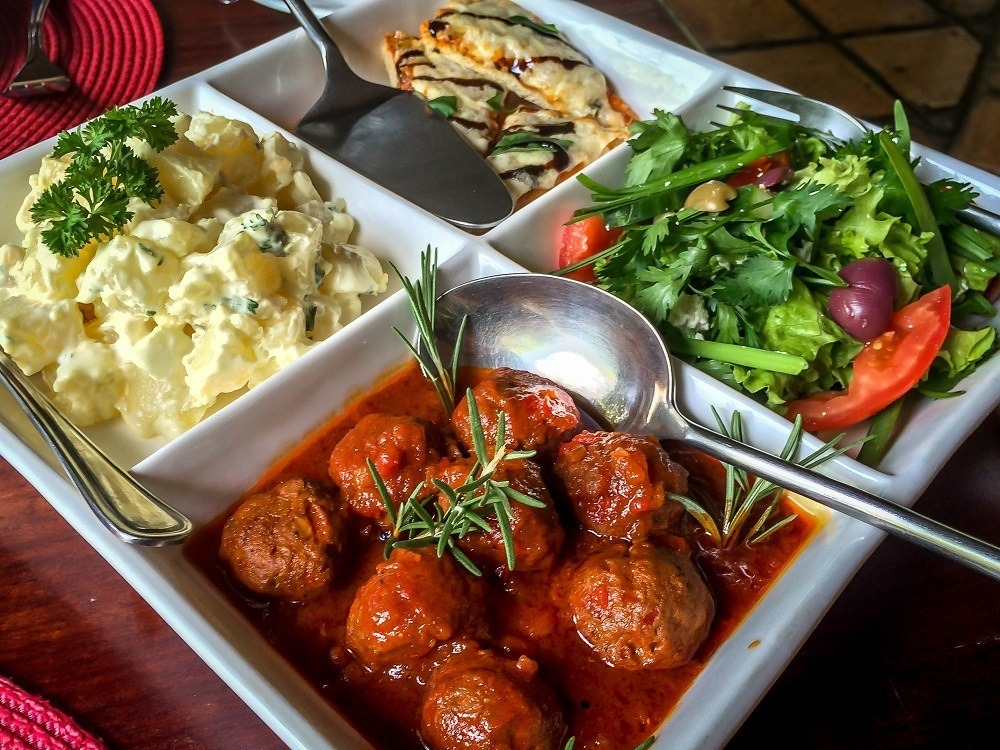 Family-style lunch of salad, potato salad, and meatballs