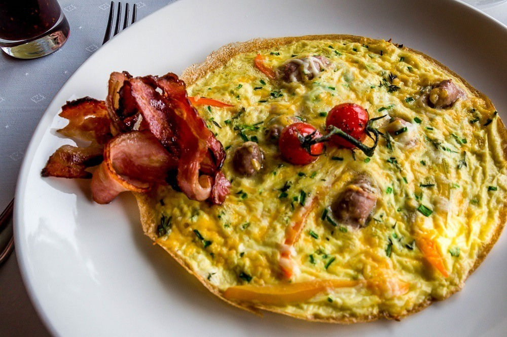 Breakfast omelet with bacon on plate