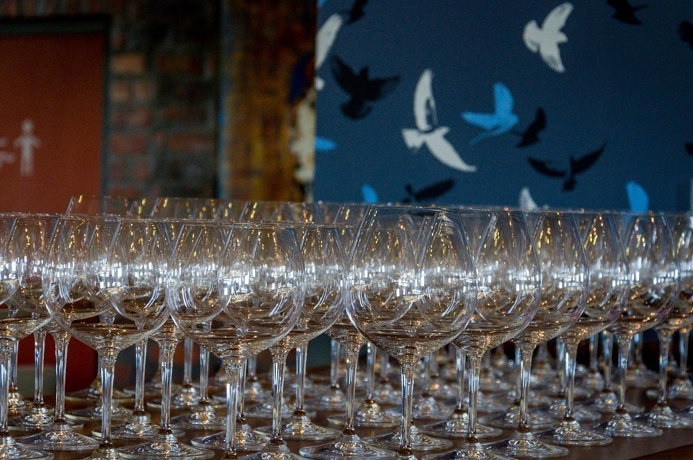 Wine glasses lined up on a bar
