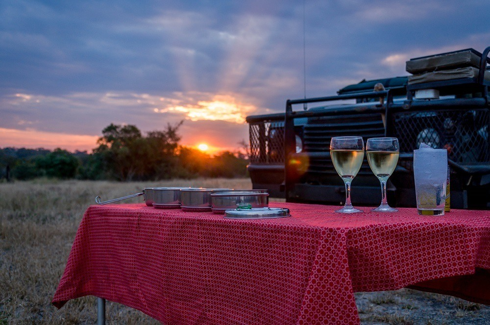 Wine glasses on red tablecloth in front of the safari Land Rover at sunset