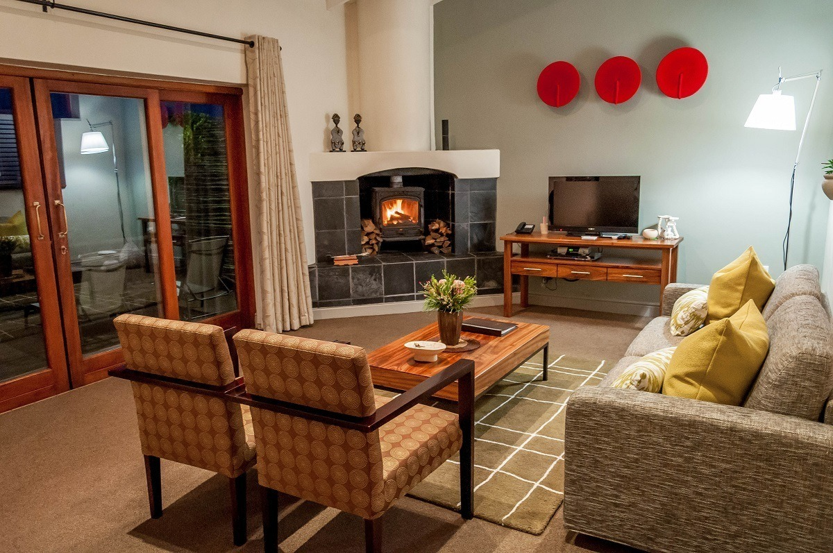 The living room with fireplace in our Grootbos Garden Lodge luxury suite