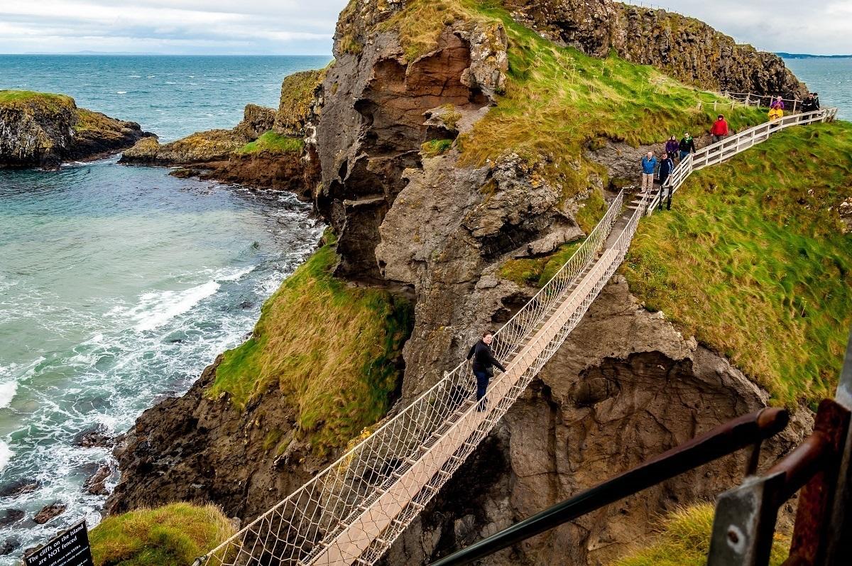 People crossing a rope bridge above the ocean
